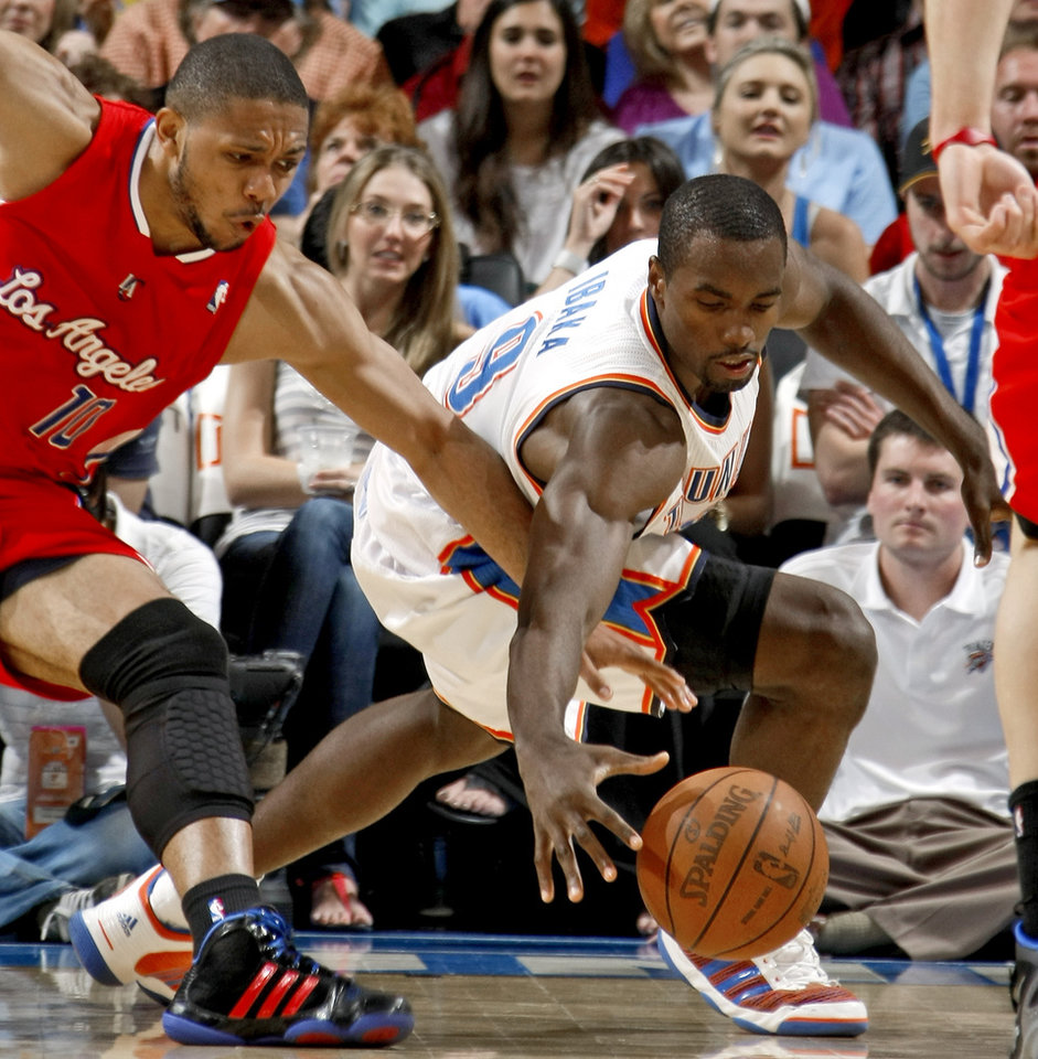 Photo - Oklahoma City's Serge Ibaka (9) goes for the ball beside Los Angeles Clippers' Eric Gordon (10) during the NBA basketball game between the Oklahoma City Thunder and the Los Angeles at the Oklahoma City Arena, Wednesday, April 6, 2011. Photo by Bryan Terry, The Oklahoman