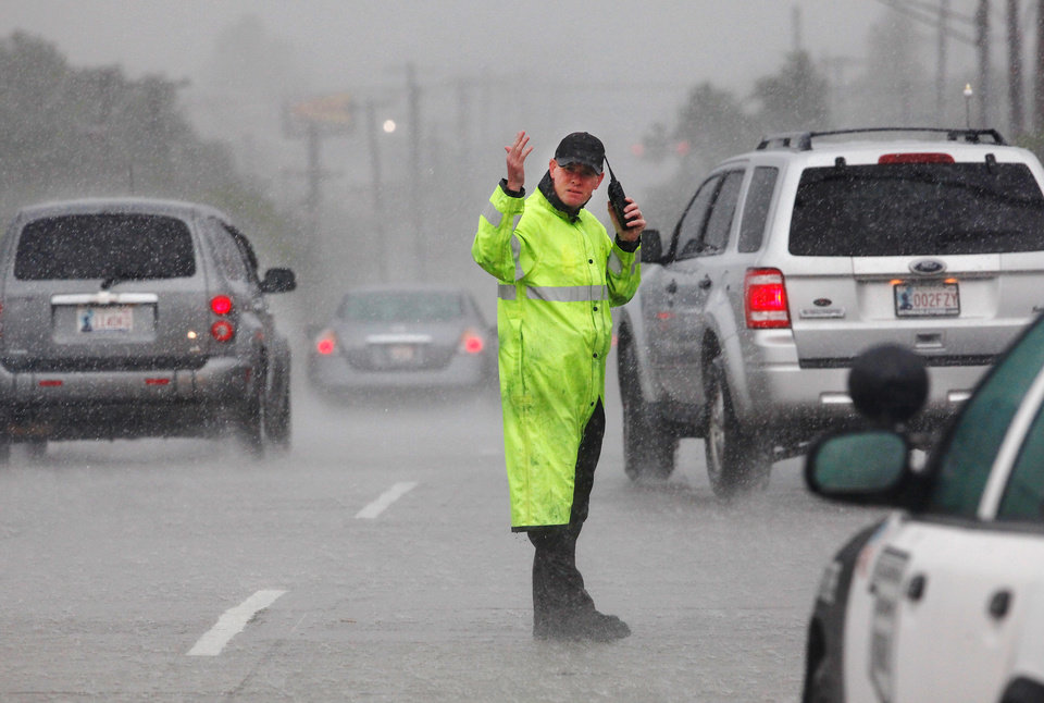 Photo - A state trooper stands in heavy rain directing traffic near Western and I-44 as traffic exits the interstate where it had come to a near standstill. Torrential rain caused flooding in Oklahoma City, Monday, June 14, 2010.     by Jim Beckel, The Oklahoman