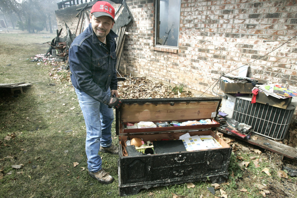 Photo - Roy Ericksen show that the contents of his daughter cedar chest survived even though her home at 14244 NE 5th was destroyed in a wildfire in Choctaw, Oklahoma April 10, 2009.  Photo by Steve Gooch, The Oklahoman