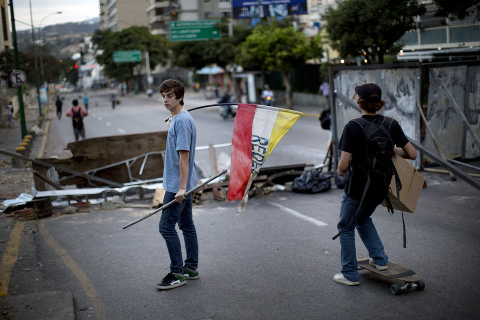 Photo - Demonstrators stand at a barricade during an opposition protest in the Altamira neighborhood of Caracas, Venezuela, Thursday, Feb. 20, 2014. Venezuelan opposition leaders condemned the government Thursday for its heavy-handed attempt to subdue a protest movement with nighttime sweeps that have turned many parts of the country into dangerous free-fire zones. (AP Photo/Rodrigo Abd)