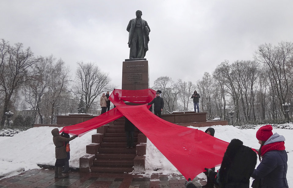 Photo - Activists hold huge red ribbon in front of the monument to Taras Shevchenko, famous Ukrainian poet to mark the 'World AIDS Day' and in memory of those who have died of AIDS in Kiev, Ukraine, Thursday, Dec. 1, 2016. (AP Photo/Efrem Lukatsky)