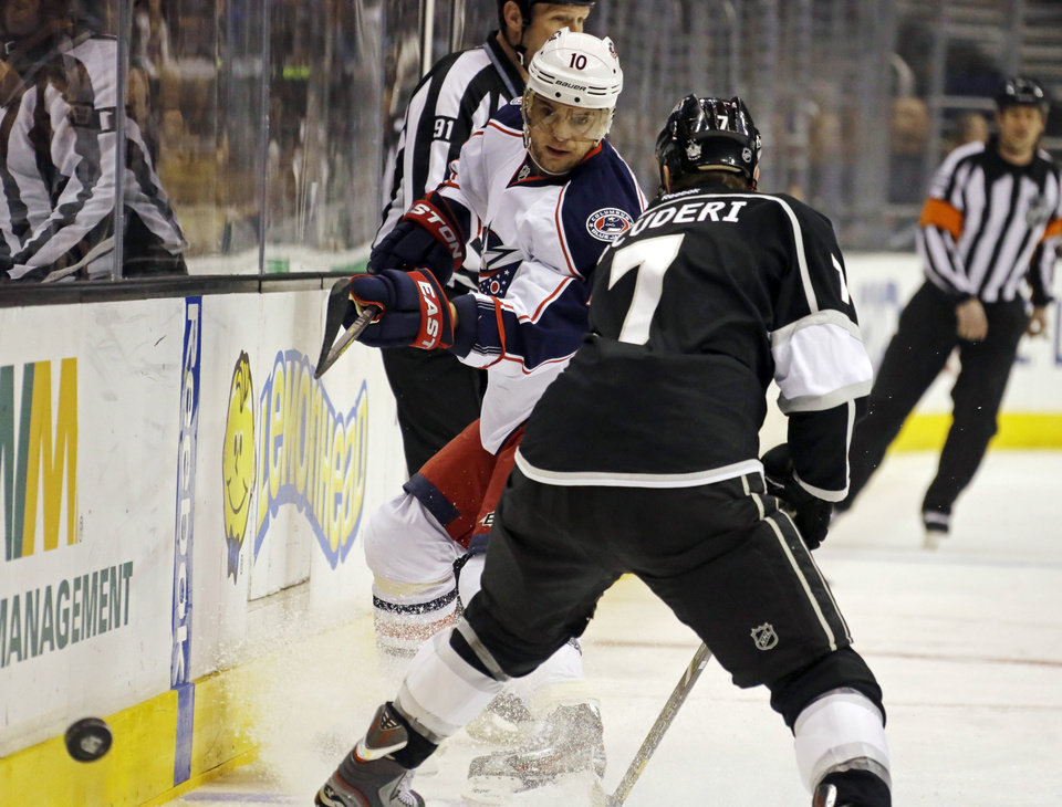 Photo - Columbus Blue Jackets right wing Marian Gaborik (10) and Los Angeles Kings defenseman Rob Scuderi (7) battle in the first period of an NHL hockey game in Los Angeles, Thursday, April 18, 2013. (AP Photo/Reed Saxon)