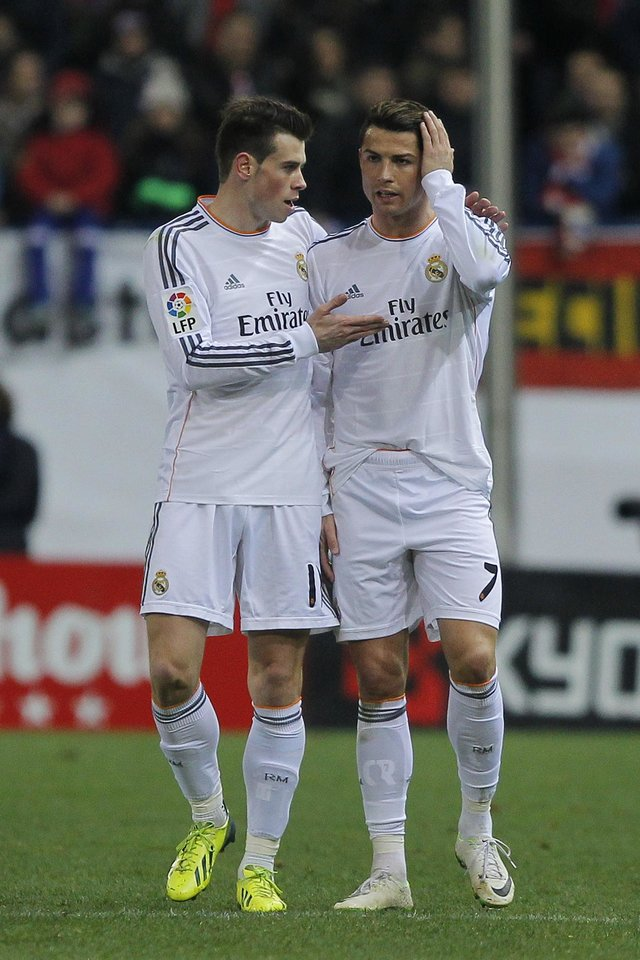 Photo - Real's Cristiano Ronaldo talks to Gareth Bale, after Ronaldo fouls Atletico's Javi Manquillo during a semi final, 2nd leg, Copa del Rey soccer match between Atletico de Madrid and Real Madrid at the Vicente Calderon stadium in Madrid, Spain, Tuesday, Feb. 11, 2014. (AP Photo/Andres Kudacki)