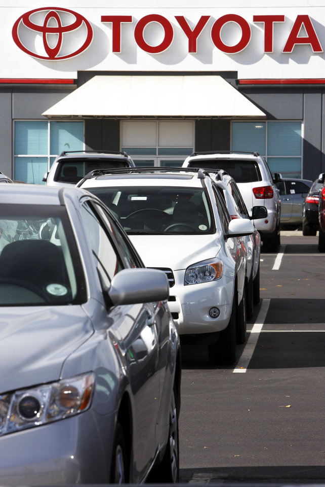 Photo - Unsold 2008 models sit Sunday under the company sign at a Toyota dealership in Centennial, Colo. AP PHOTO