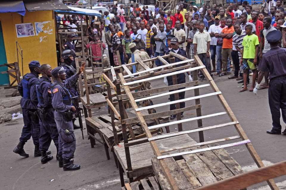 Photo - Liberia security forces blockade an area around the West Point Ebola center as the government clamps down on the movement of people to prevent the spread of the Ebola virus in the city of Monrovia, Liberia, Wednesday, Aug. 20, 2014. Security forces deployed Wednesday to enforce a quarantine around a slum in the Liberian capital, stepping up the government's fight to stop the spread of Ebola and unnerving residents. (AP Photo/Abbas Dulleh)
