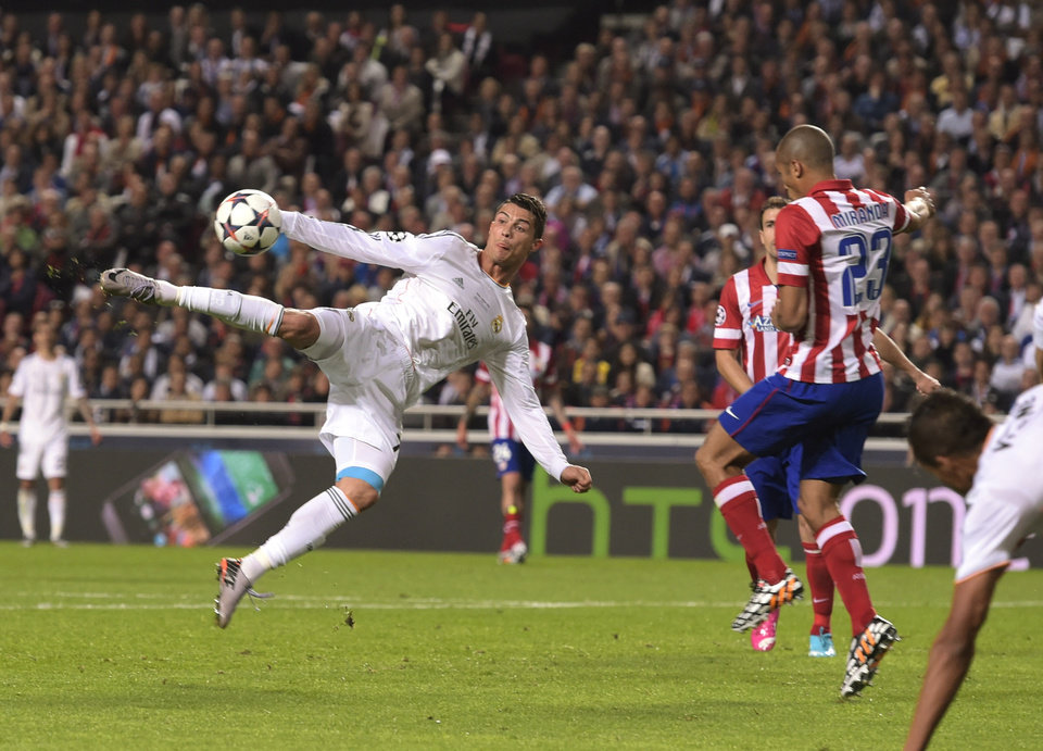 Photo - Real's Cristiano Ronaldo kicks the ball near to Atletico's Miranda during the Champions League final soccer match between Atletico Madrid and Real Madrid, at the Luz stadium, in Lisbon, Portugal, Saturday, May 24, 2014. (AP Photo/Manu Fernandez)