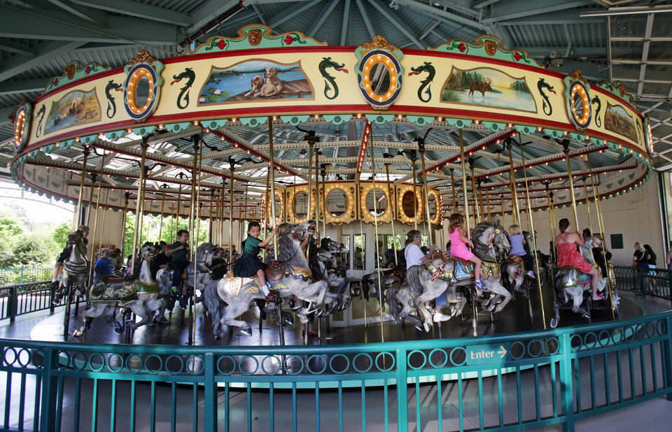 Photo - In this photo taken Tuesday, June 3, 2014, visitors to the Como Town amusement park ride on the 100-year-old Cafesjian's Carousel in St. Paul, Minn. Parking at the Como Town and adjacent Como Park Zoo and Conservatory is free but there is a charge to ride the Carousel. (AP Photo/Jim Mone)