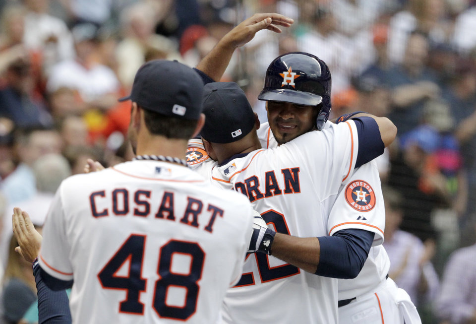 Photo - Houston Astros' Jesus Guzman, right, is congratulated by teammates after hitting a two-run home run in the first inning of a baseball game against the New York Yankees, Tuesday, April 1, 2014, in Houston. (AP Photo/Patric Schneider)