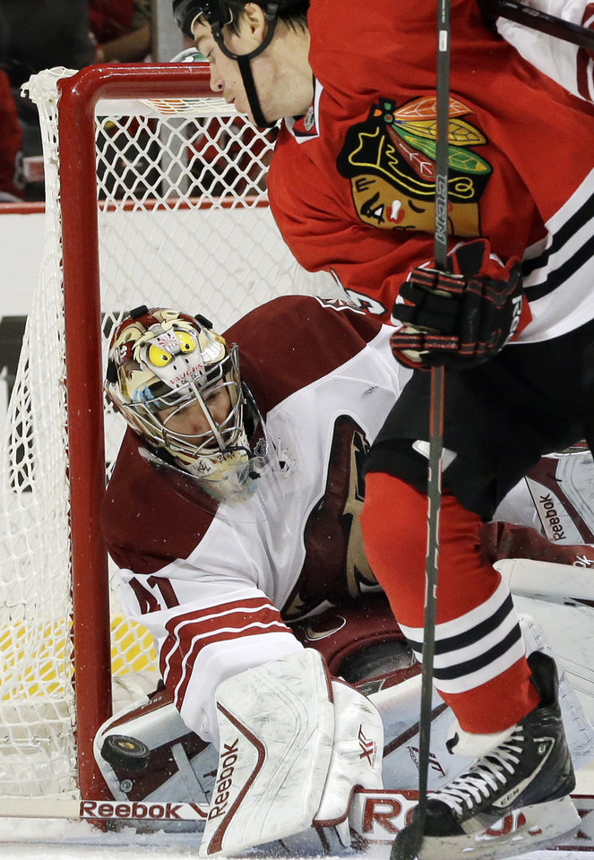 Phoenix Coyotes goalie Mike Smith, left, blocks a shot by Chicago Blackhawks' Andrew Shaw during the second period of an NHL hockey game in Chicago, Thursday, Nov. 14, 2013. (AP Photo/Nam Y. Huh)