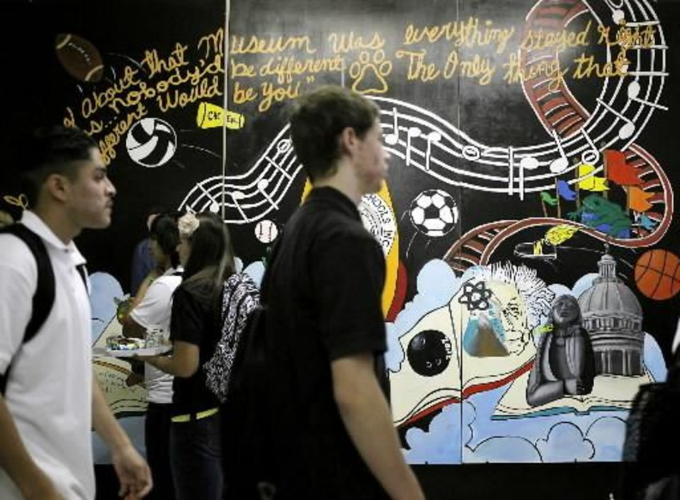 "Students file to and from the cafeteria during their lunch period under a quote from the novel ""The Catcher in the Rye"" painted on a mural in the main hallway during the first day of school at Santa Fe South Charter School in south Oklahoma City on Thursday, Aug. 4, 2011. Photo by John Clanto"