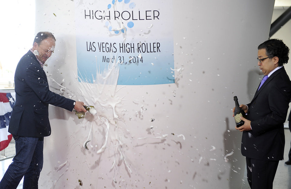 Photo - David Codiga, left,  executive project director of The LINQ breaks a bottle of champagne as Tariq Shaukat, chief marketing officer of Caesars Entertainment looks on during the opening of the Las Vegas High Roller at The LINQ on March 31, 2014, in Las Vegas. The 550-foot-tall attraction, which opened to the public today, is the highest observation wheel in the world and features 28 cabins that can accommodate up to 40 people each. (AP Photo/David Becker)