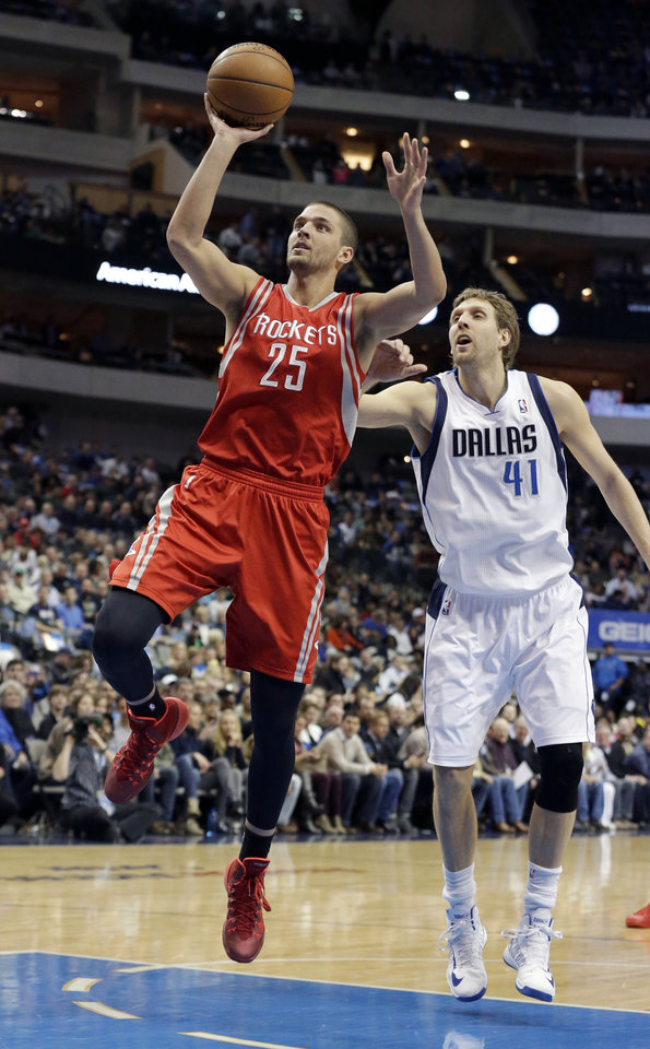 Photo - Houston Rockets forward Chandler Parsons (25) drives past Dallas Mavericks forward Dirk Nowitzki (41), of Germany, during the first half of an NBA basketball game Wednesday, Jan. 29, 2014, in Dallas. (AP Photo/LM Otero)