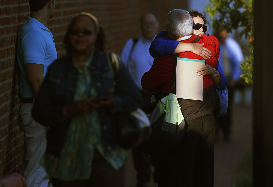 Photo - A woman hugs a man before entering the Washington Navy Yard as employees return to work, Thursday, Sept. 19, 2013. The Washington Navy Yard returned to nearly normal operations three days after it was the scene of a mass shooting in which a gunman killed 12 people. (AP Photo/Charles Dharapak)