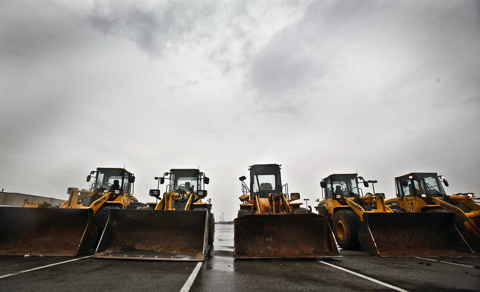 Photo - Tractors stage in a parking lot as crews prepare for the severity of the winter weather conditions that are forecasted for the state on Thursday, Jan. 28, 2010, in Yukon, Okla.   Photo by Chris Landsberger, The Oklahoman