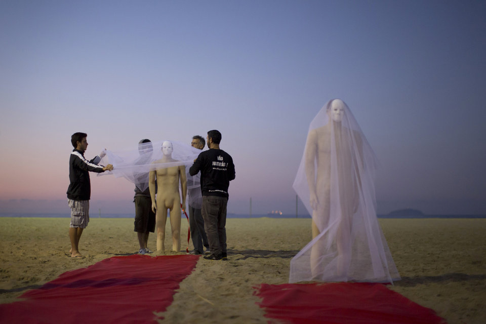Photo - Rio de Paz activists wrap a mannequin in a veil during a protest on Copacabana beach to press for clarifications on missing persons including a bricklayer who recently disappeared, in Rio de Janeiro, Brazil, Wednesday, July 31, 2013. The 42-year-old father of six was picked up for police questioning on suspicions of involvement in drug trafficking, but was released shortly thereafter. He has not been seen from since. Rio de Paz organization cites official statistics showing that nearly 35,000 people were reported as missing in Rio state alone over the past five years. (AP Photo/Felipe Dana)