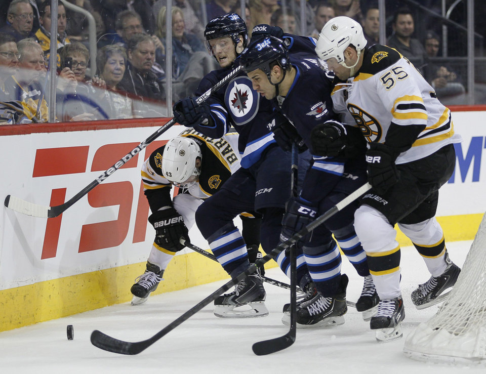 Photo - Boston Bruins' Matt Bartkowski (43) and Johnny Boychuk (55) scramble with Winnipeg Jets' Carl Klingberg, center left, and Patrice Cormier for the puck behind the Bruins' net during the second period of an NHL hockey game Thursday, April 10, 2014, in Winnipeg, Manitoba. (AP Photo/The Canadian Press, John Woods)