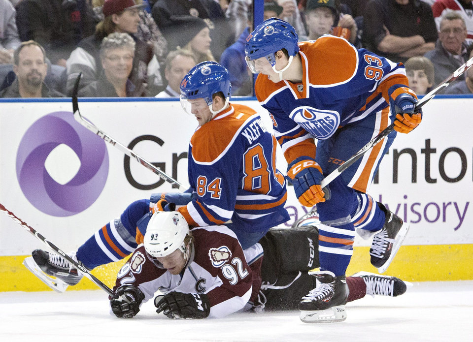 Photo - Colorado Avalanche's Gabriel Landeskog (92) is knocked down by Edmonton Oilers' Oscar Klefbom (84) and Ryan Nugent-Hopkins (93) during first period NHL hockey action in Edmonton, Alberta, on Tuesday April 8, 2014. (AP Photo/The Canadian Press, Jason Franson)