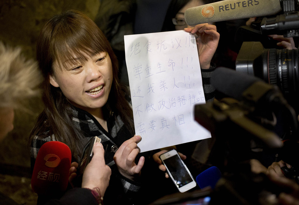 Photo - A relative of a Chinese passenger aboard the missing Malaysia Airlines Flight MH370 shows a paper reading