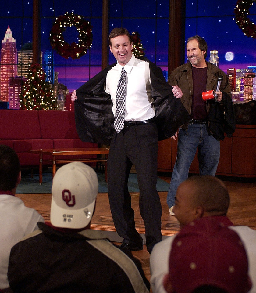 Photo - OU COLLEGE FOOTBALL: Oklahoma football coach Bob Stoops dances in front of members of his team as