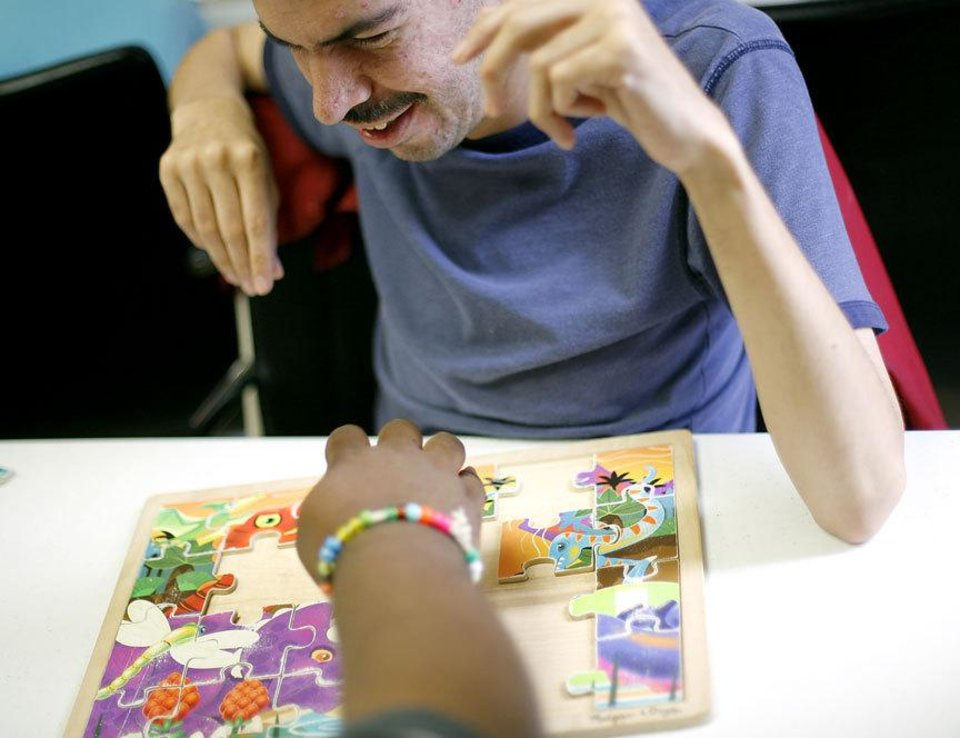 Photo - Michael Avila, 38, works on a children's puzzle with a friend at Metropolitan Better Living Center in Oklahoma City on Tuesday, June 9, 2009. Michael, who has cerebral palsy and can't speak, works puzzles everyday with another man who can't speak.  Photo by John Clanton, The Oklahoman