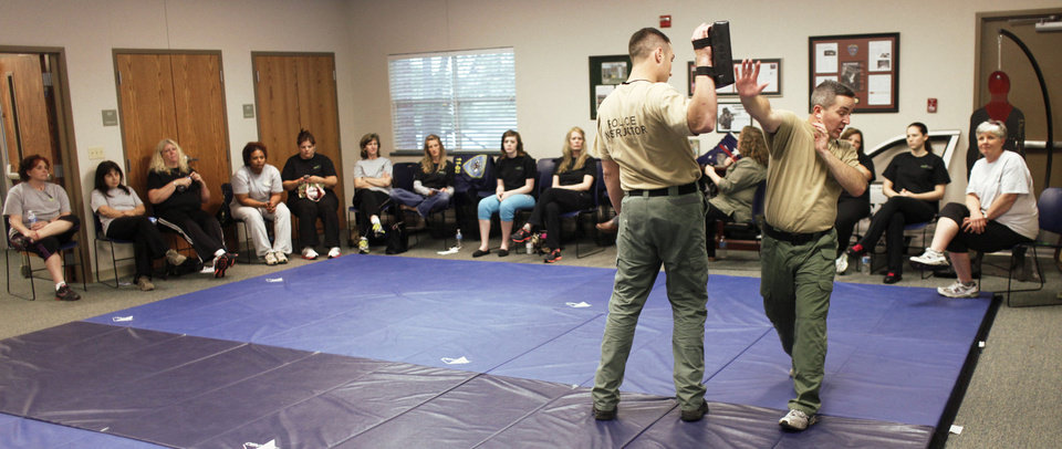 Photo - Instructors Ben Daves, left, and Sgt. Jeff Richardson demonstrate one of the moved taught during a four-week self-defense class for city female employees.  PHOTOS BY DOUG HOKE, THE OKLAHOMAN