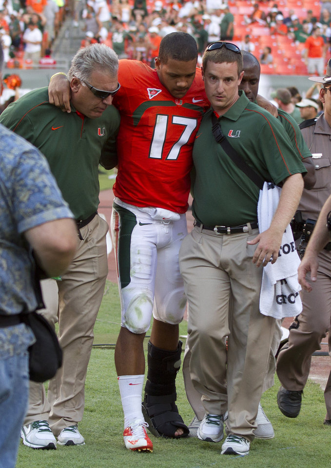 Miami quarterback Stephen Morris (17) is helped off the field during the second half of a NCAA college football game in Miami, Saturday, Oct. 13, 2012 against North Carolina. North Carolina won 18-14. (AP Photo/J Pat Carter)