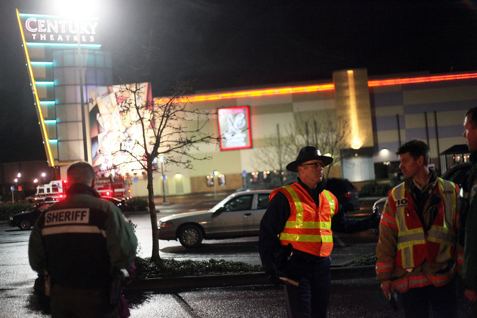 Photo - Authorities stand by in the parking lot of Clackamas Town Center in Portland, Ore., Tuesday, Dec. 11, 2012. A gunman opened fire in the suburban Portland shopping mall Tuesday, killing two people and wounding another as people were doing their Christmas shopping, authorities said. (AP Photo/Statesman-Journal, Thomas Patterson)