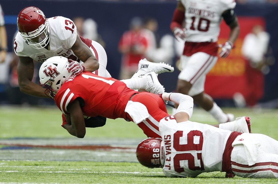 Photo - Oklahoma's Ahmad Thomas (13) and Jordan Evans (26) bring down Houston's Greg Ward Jr. (1) during the AdvoCare Texas Kickoff college football game between the University of Oklahoma Sooners (OU) and the Houston Cougars at NRG Stadium in Houston, Saturday, Sept. 3, 2016. Houston won 33-23. Photo by Bryan Terry, The Oklahoman