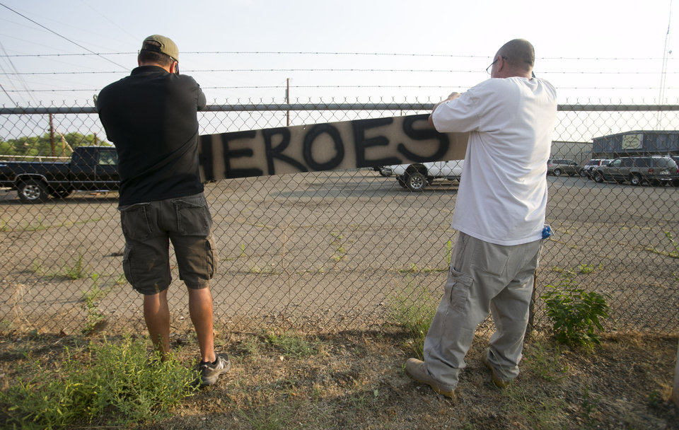 Photo - Two men place a hero sign in front of Prescott Fire Station #7 on Monday, July 1, 2013, in Prescott, Ariz.  Eighteen firefighters from the Prescott Fire Department's Granite Mountain Hotshots team and a 19th firefighter from another crew were killed battling the Yarnell Hill Fire on Sunday. The Granite Mountain Hotshots were based out of Prescott Fire Station #7. David Wallace/The Arizona Republic  (AP Photo/The Arizona Republic, Dasvid Wallace)  MARICOPA COUNTY OUT; MAGS OUT; NO SALES