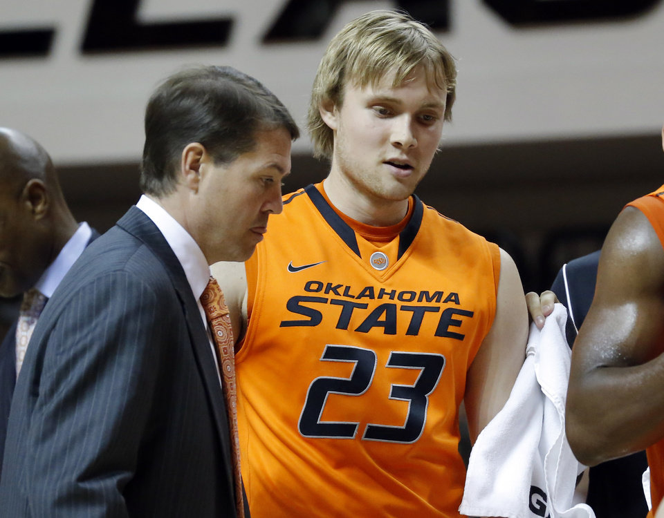 Photo - Oklahoma State coach Travis Ford stands next to Alex Budke during a timeout during the college basketball game between Oklahoma State University and Ottawa (Kan.) at Gallagher-Iba Arena in Stillwater, Okla., Thursday, Nov. 1, 2012. Photo by Sarah Phipps, The Oklahoman