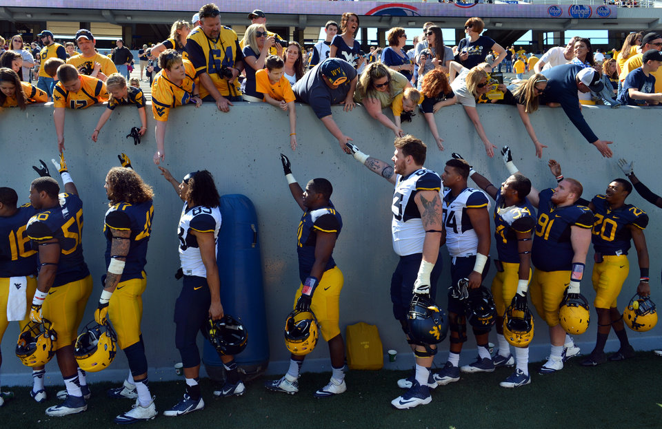 Photo - West Virginia players high-fives fans after their spring NCAA college football game in Morgantown, W.Va., Saturday, April 12, 2014. (AP Photo/Craig Cunningham)