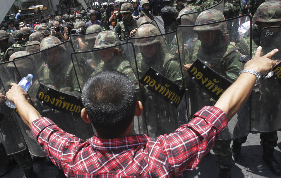 Photo - An anti-coup demonstrator gestures in front of Thai soldiers during a protest in Bangkok, Thailand, Sunday, May 25, 2014. Gen. Prayuth Chan-ocha in Thailand's ruling junta warned people Sunday not to join anti-coup street protests, saying normal democratic principles cannot be applied at the time, as troops fanned out in central Bangkok to prevent rallies.(AP Photo/Sakchai Lalit)
