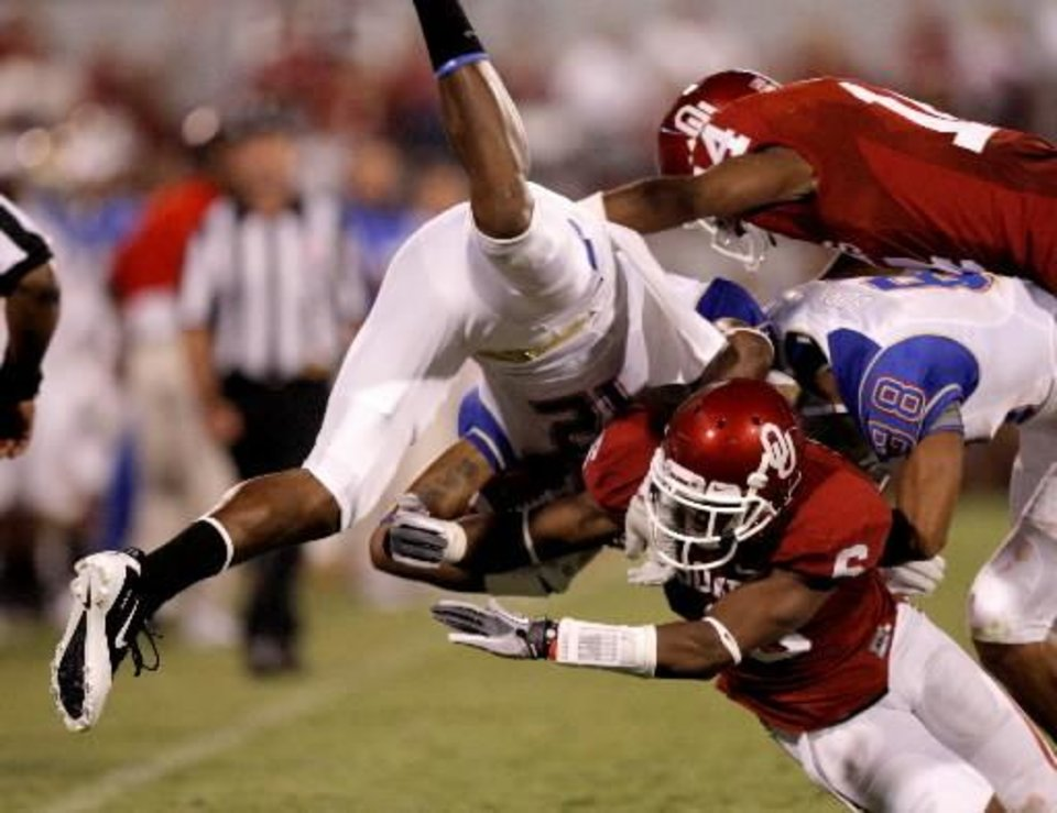 Photo - Oklahoma's Demontre Hurst (6) and Aaron Colvin (14) bring down Tulsa's Jordan James (12) during the college football game between the University of Oklahoma Sooners ( OU) and the Tulsa University Hurricanes (TU) at the Gaylord Family-Memorial Stadium on Saturday, Sept. 3, 2011, in Norman, Okla. Oklahoma won 47-14. Photo by Bryan Terry, The Oklahoman ORG XMIT: KOD