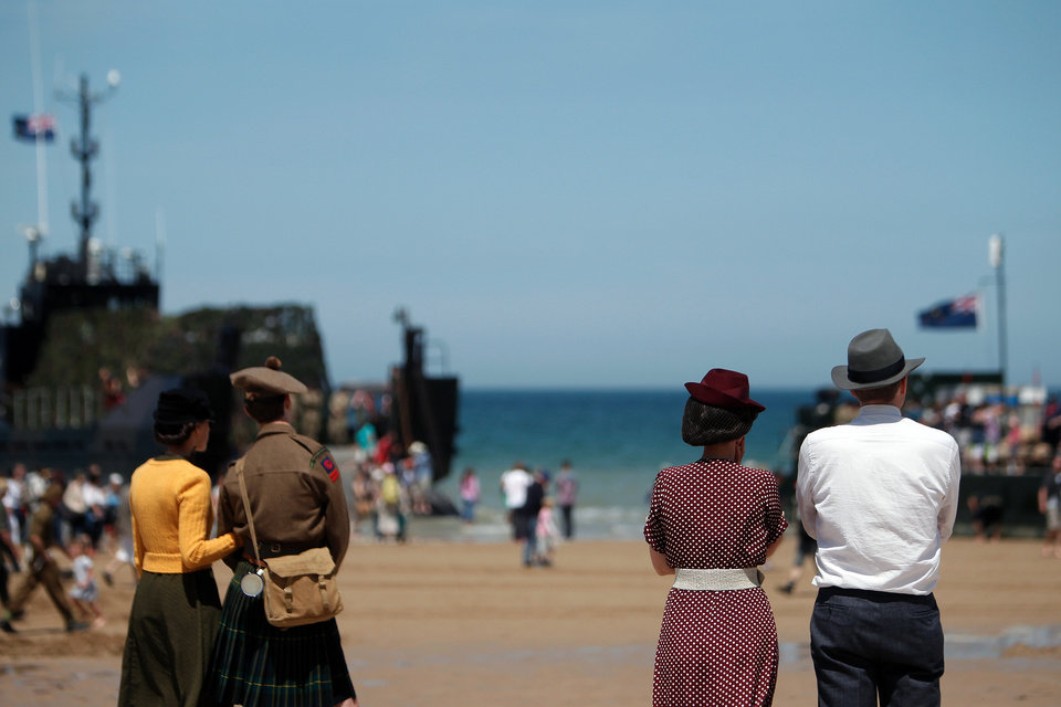 Photo - People wearing WWII style clothes look toward the sea, on the beach of Arromanches, western France, Friday June 6, 2014.  Ceremonies to commemorate the 70th anniversary of D-Day are drawing thousands of visitors to the cemeteries, beaches and stone-walled villages of Normandy this week, including some of the few remaining survivors of the largest sea-borne invasion ever mounted. (AP Photo/Thibault Camus)
