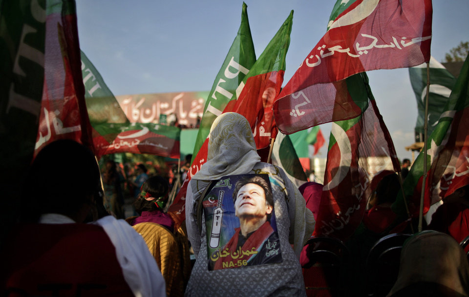 Photo - Pakistani supporters of former cricket star-turned-politician, and leader of Pakistan Tehreek-e-Insaf party, Imran Khan, wave his party's flag during a rally in Islamabad, Pakistan, Thursday, May 9, 2013. Pakistan is scheduled to hold parliamentary elections on May 11, the first transition between democratically elected governments in a country that has experienced three military coups and constant political instability since its creation in 1947. The parliament's ability to complete its five-year term has been hailed as a significant achievement. (AP Photo/Muhammed Muheisen)