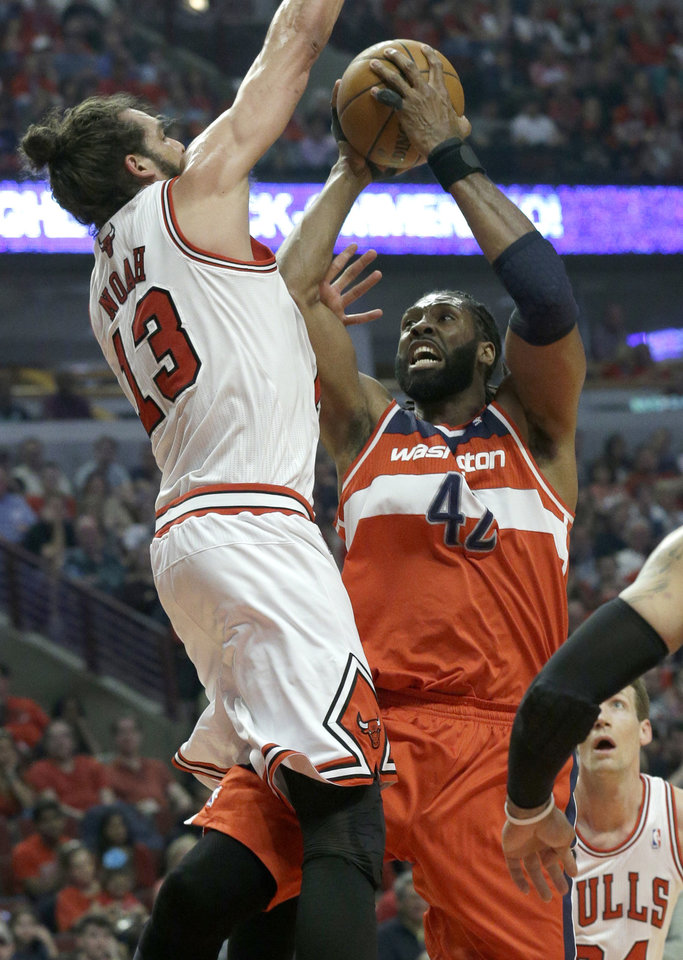Photo - Washington Wizards forward Nene, right, drives to the basket against Chicago Bulls center Joakim Noah during the first half in Game 1 of an opening-round NBA basketball playoff series in Chicago, Sunday, April 20, 2014. (AP Photo/Nam Y. Huh)