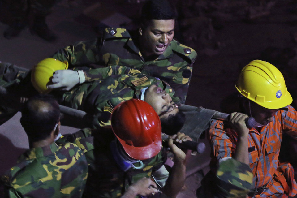 Photo - Bangladeshi soldiers and firefighters carry an injured colleague after a fire in a tunnel rescue workers were using to search for survivors in a building that collapsed Wednesday in Savar, near Dhaka, Bangladesh, Sunday, April 28, 2013. A fire broke out late Sunday in the wreckage of the garment factory that collapsed last week in Bangladesh killing hundreds, with smoke pouring from the piles of shattered concrete and some of the rescue efforts forced to stop.(AP Photo/Kevin Frayer)