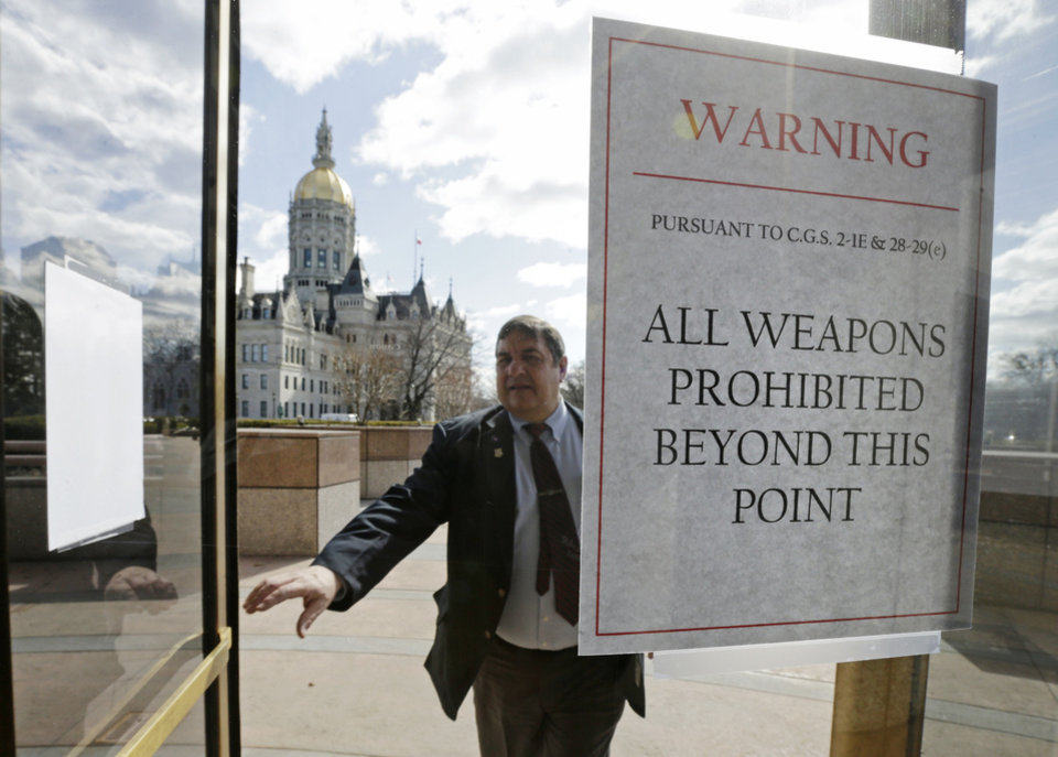 A Capitol security officer enters a revolving door at the legislative office building, with a sign warning not to bring weapons on to the grounds at the Capitol in Hartford, Conn., Wednesday, April 3, 2013. Hundreds of gun rights advocates are gathering at the statehouse in Hartford ahead of a vote in the General Assembly on proposed gun-control legislation. (AP Photo/Charles Krupa)