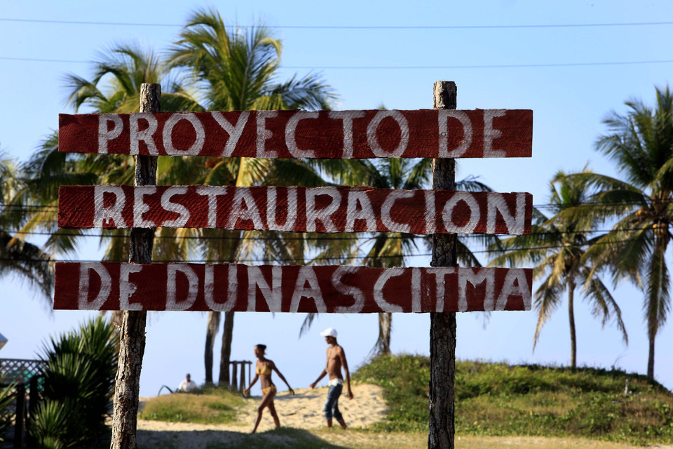 Photo - In this May 24, 2013 photo, people walk on the beach behind a sign that reads in Spanish