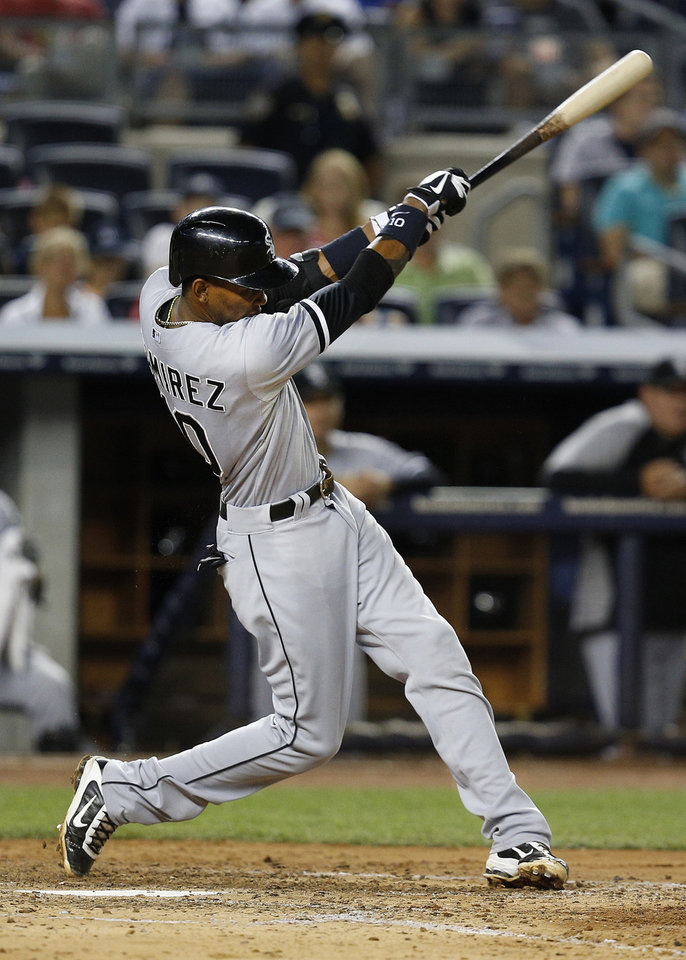 Photo - Chicago White Sox's Alexei Ramirez hits a two-run triple to drive home Alejandro De Aza and Gordon Beckham in the fifth inning of a baseball game against the New York Yankees at Yankee Stadium, Tuesday, Sept. 3, 2013, in New York. (AP Photo/John Minchillo)