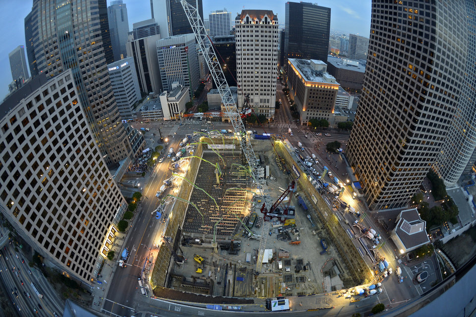 Photo - In this Ariel photo made with a fisheye lens, crews pour concrete to lay the foundation for the New Wilshire Grand building in a record attempt for the largest continuous concrete pour in history, Saturday, Feb. 15, 2014, in downtown Los Angeles. The marathon pour is expected to last 20 hours without interruption. The attempt will be verified by an official from Guinness World Records. The New Wilshire Grand will be the tallest building to be built west of the Mississippi and is expected to be completed in 2017. (AP Photo/Mark J. Terrill)