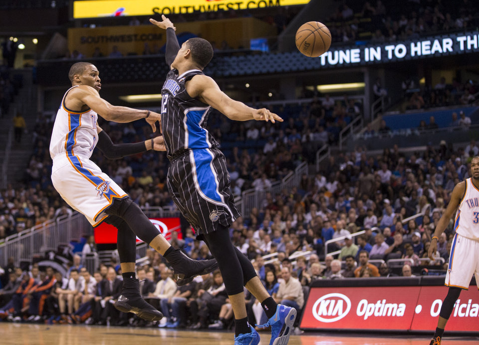 Photo - Oklahoma City Thunder's Russell Westbrook (0) passes the ball as Orlando Magic's Tobias Harris (12) defends on the play during the second half of an NBA basketball game on Friday, March 22, 2013, in Orlando, Fla. The Thunder won 97-89.  (AP Photo/Willie J. Allen Jr.) ORG XMIT: FLWA105