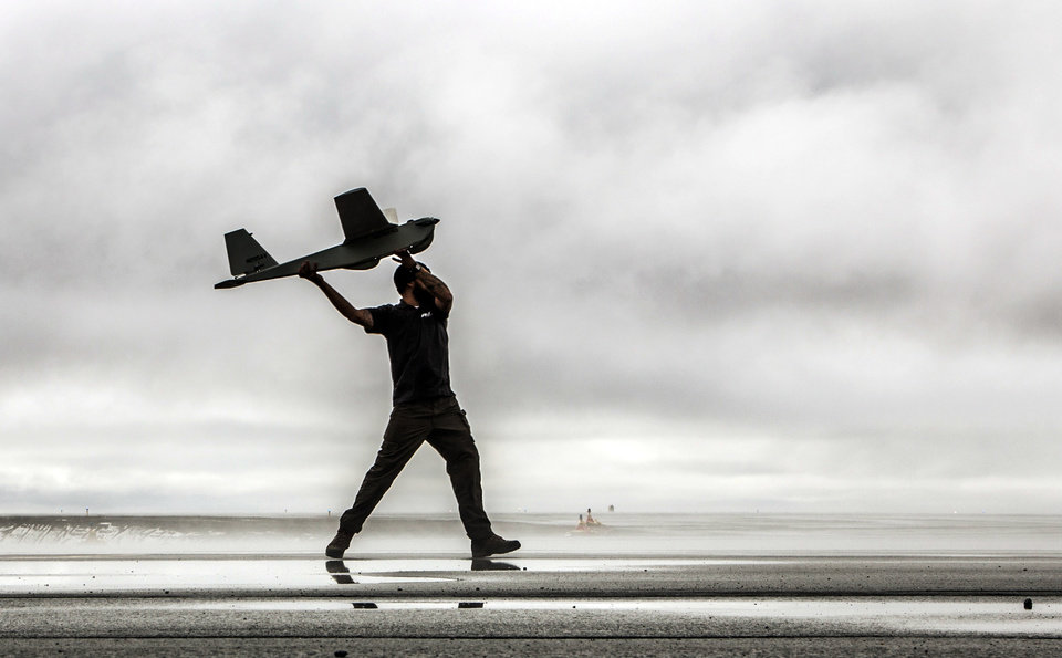Photo - In this undated photo provided by AeroVironment, a man hand-launches a Puma drone aricraft. The Federal Aviation Administration (FAA) said Tuesday, June 10, 2014 it has granted the first permission for commercial drone flights over land, the latest effort by the agency to show it is loosening restrictions on commercial uses of the unmanned aircraft. Drone maker AeroVironment of Monrovia, Calif., and BP energy corporation have been given permission to use a Puma drone to survey pipelines, roads and equipment at Prudhoe Bay in Alaska, the agency said. The first flight took place on Sunday. The Puma is a small, hand-launched craft about 4 1/2 feet long and with a 9-foot wingspan. It was initially designed for military use. (AP Photo/AeroVironment)
