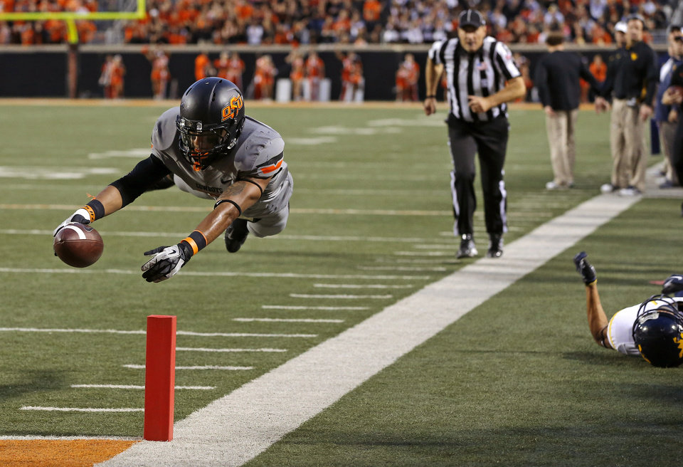 Photo - Oklahoma State's Josh Stewart (5) leaps for a touchdown during a college football game between Oklahoma State University (OSU) and West Virginia University at Boone Pickens Stadium in Stillwater, Okla., Saturday, Nov. 10, 2012. Oklahoma State won 55-34. Photo by Bryan Terry, The Oklahoman