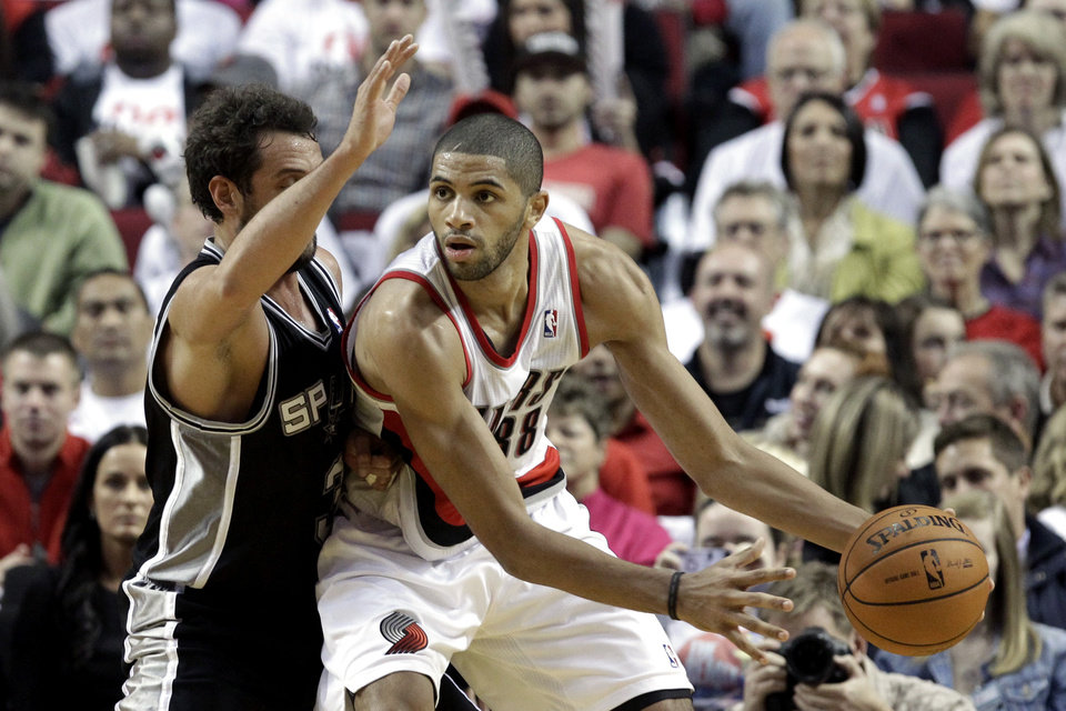 Photo - Portland Trail Blazers forward Nicolas Batum, right, from France,  looks to pass against San Antonio Spurs guard Marco Belinelli, from Italy, during the second half of an NBA basketball game in Portland, Ore., Saturday, Nov. 2, 2013. Batum   scored a triple-double as they defeated the Spurs 115-105.  (AP Photo/Don Ryan)