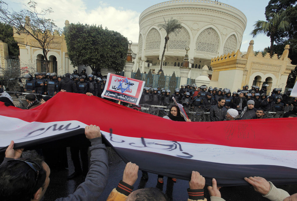 Photo - Egyptians wave a giant flag during anti-President Mohammed Morsi protest in front of the presidential palace in Cairo, Egypt, Friday, Feb. 1, 2013. Arabic reads