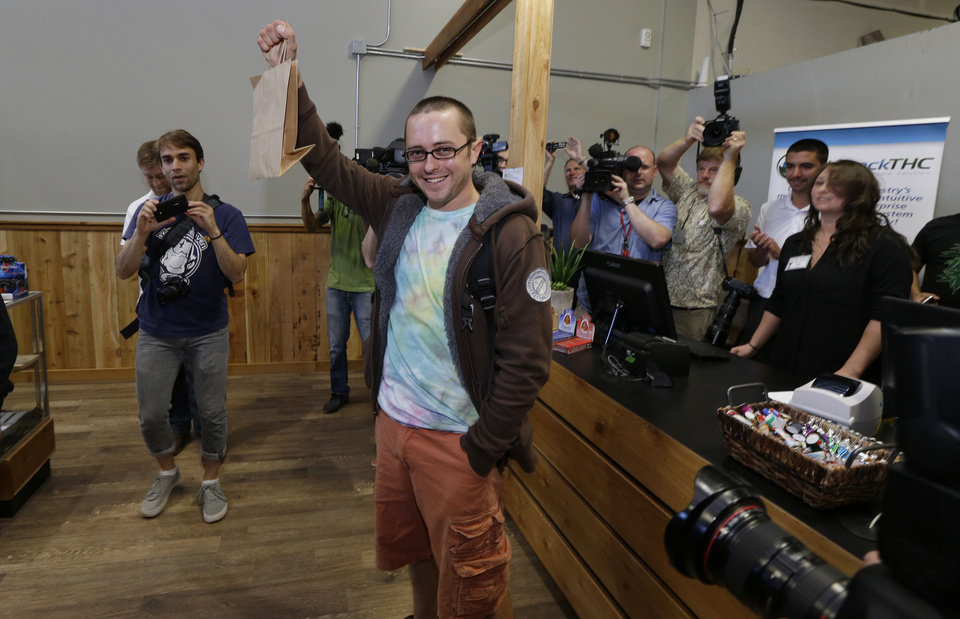 Photo - Cale Holdsworth, of Abeline, Kan., holds up his purchase after being the first in line to buy legal recreational marijuana at Top Shelf Cannabis, Tuesday, July 8, 2014, in Bellingham, Wash. Holdsworth had been in line since 4:00 a.m. (AP Photo/Ted S. Warren)
