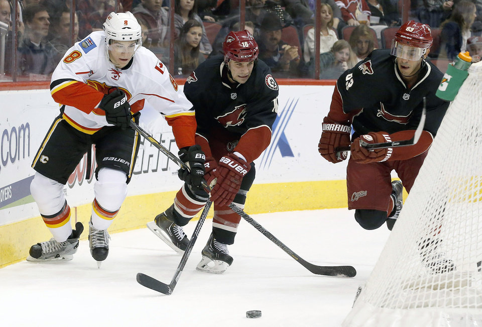 Photo - Calgary Flames' Joe Colborne (8) battles Phoenix Coyotes' Rostislav Klesla (16), of the Czech Republic, and Mike Ribeiro (63) for the puck during the first period of an NHL hockey game, Tuesday, Jan. 7, 2014, in Glendale, Ariz. (AP Photo/Ross D. Franklin)