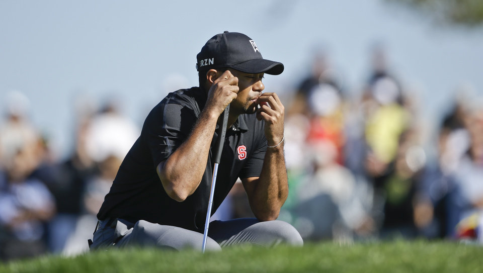 Photo - Tiger Woods waits his turn on the second green of the South Course at Torrey Pines during the third round of the Farmers Insurance Open golf tournament Saturday, Jan. 25, 2014, in San Diego.  (AP Photo/Lenny Ignelzi)