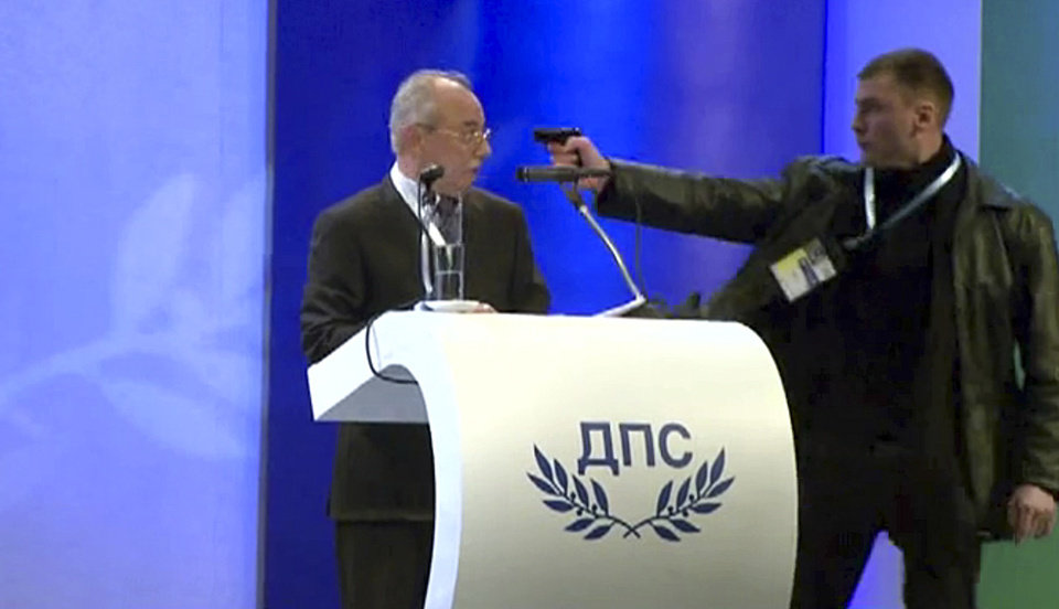 Image grab from video shows a man identified as Oktai Enimehmedov, 25, as he points a weapon at Ahmed Dogan, left, leader of the Movement for Rights and Freedoms, during his speech at his party's congress in Sofia, on Saturday Jan. 19, 2013. Dogan struck the man before other delegates wrestled the assailant to the ground, and no shots were fired.  Police took the man away.(AP Photo/ BTVnews)